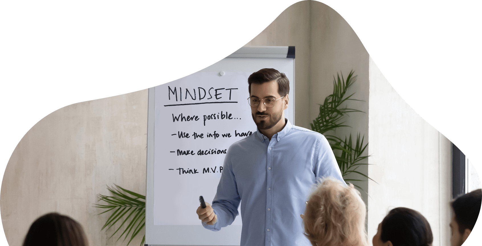 Man stood in front of a whiteboard talking to people in a room
