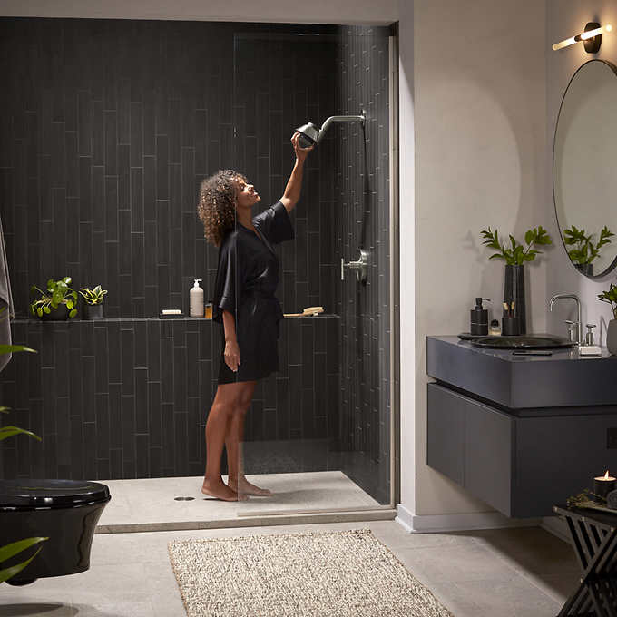 an image of a Black woman with brown hair standing inside a shower. She is reaching up and holding the showerhead. The shower has black tile walls and a glass shower door. There are plants in the shower and all around the bathroom.�