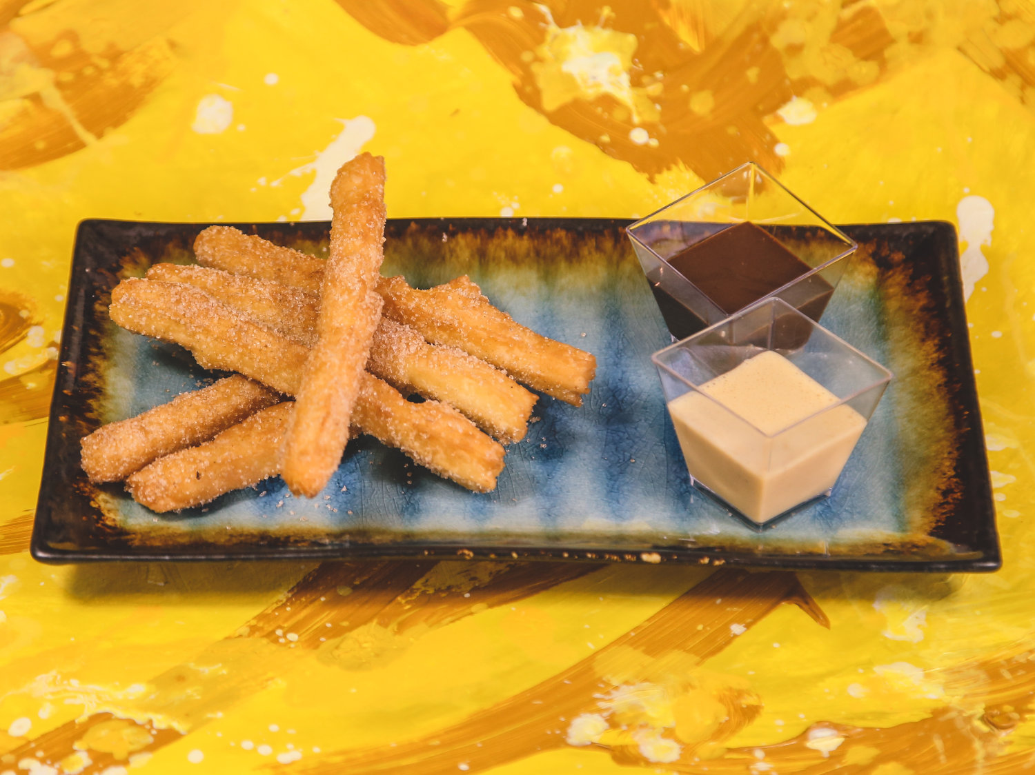 Spanish dessert made of fried dough sprinkled with sugar and cinnamon with caramel and chocolate sauce