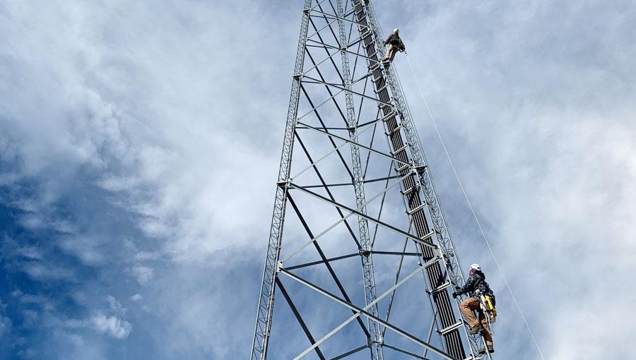 man climbing radio cell towers