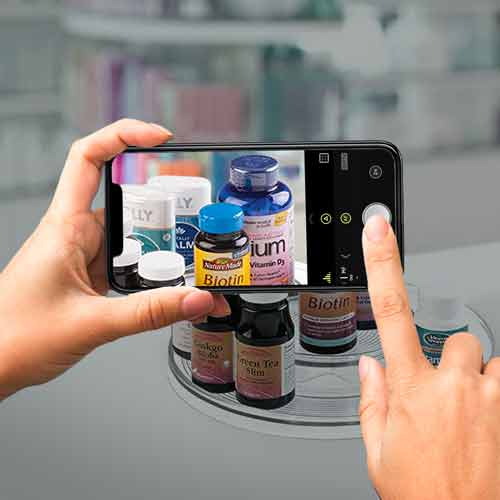 Image of pharmacist taking a photo of the vitamins on the pharmacy counter