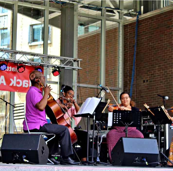 Musicians sitting onstage playing string instruments during the Chattanooga Festival of Black Arts and Ideas.