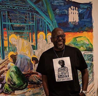 Artist smiling in front of artwork.