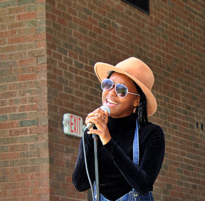 Singer onstage singing into a microphone.