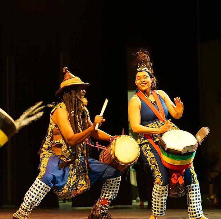 Performers drumming and dancing onstage.
