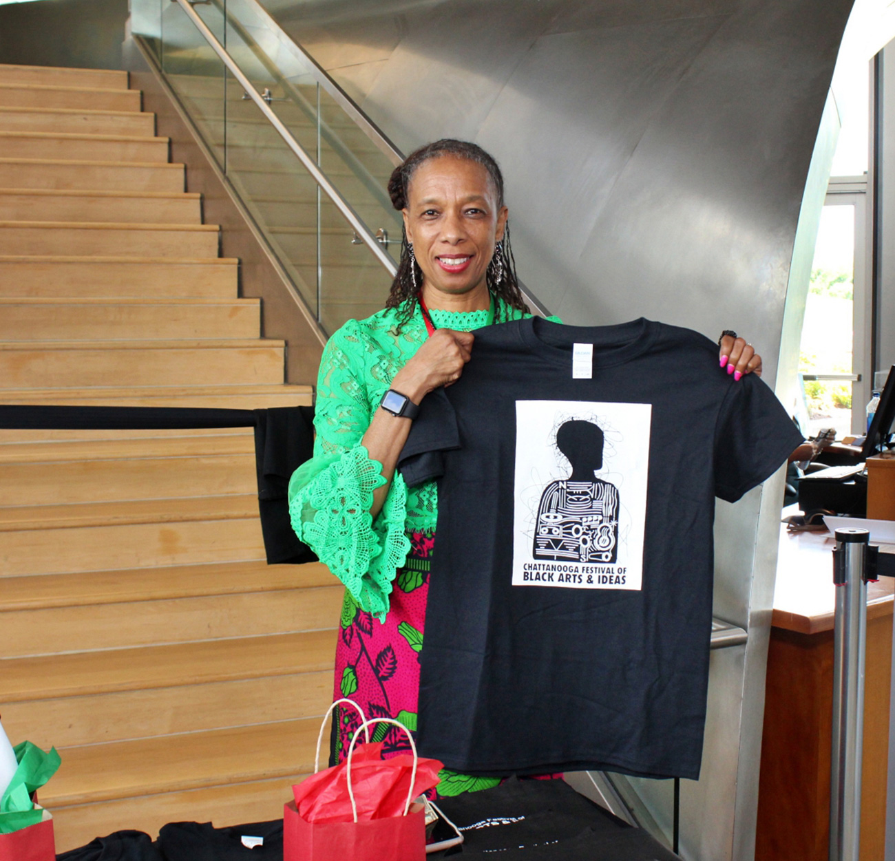 Volunteer holding up a Chattanooga Festival of Black Arts and Ideas shirt.