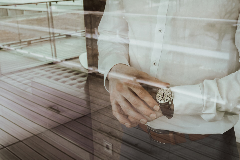 Ein Business Mensch in Hemd vor einem Fenster mit schöner Armbanduhr