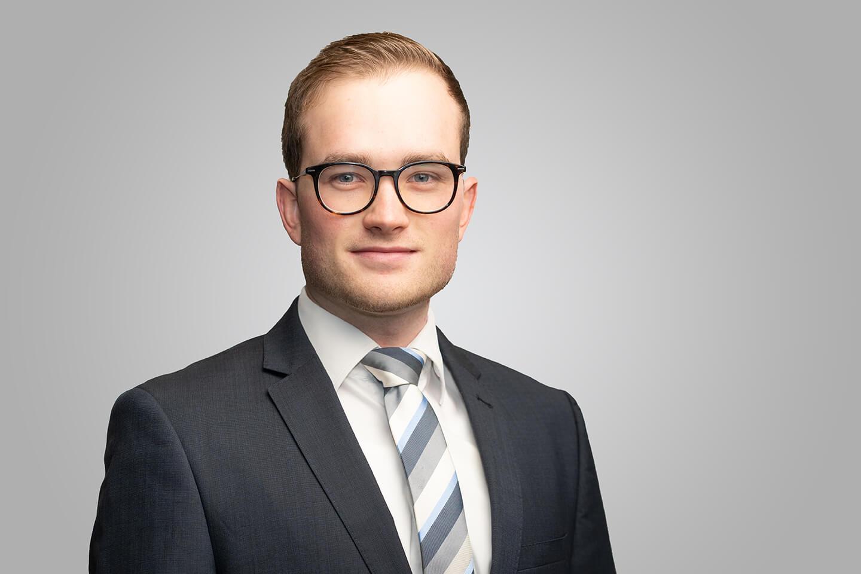 Ein Portraitfoto von einem jungen Mann in Anzug vor grauem Hintergrund