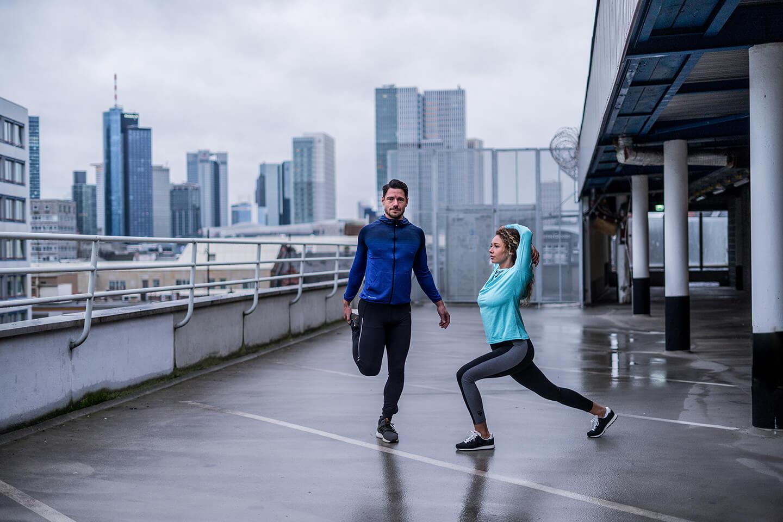 Ein sportliches Paar, das Fitnessübungen auf einem Parkdeck vor der Frankfurter Skyline macht