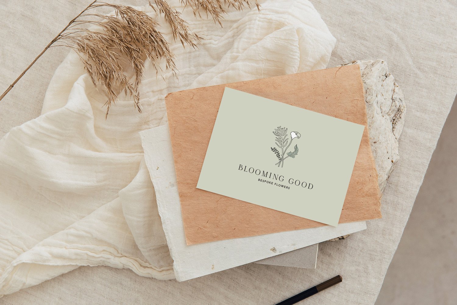 Feminine logo illustration printed on a card with a linen background