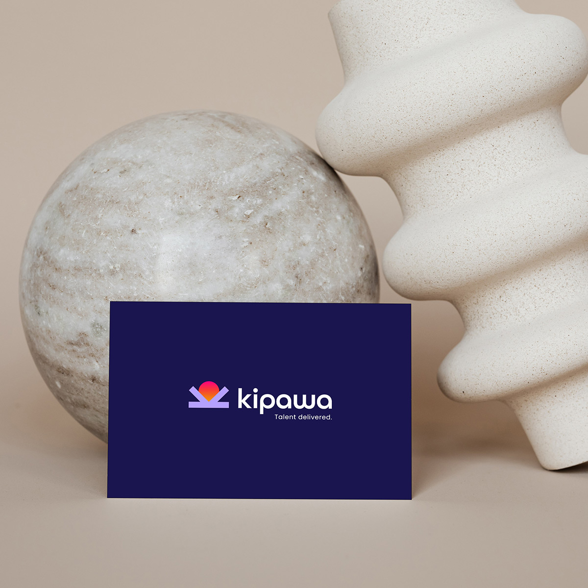 Business card for recruitment agency in Kenya propped up next to earthy vase