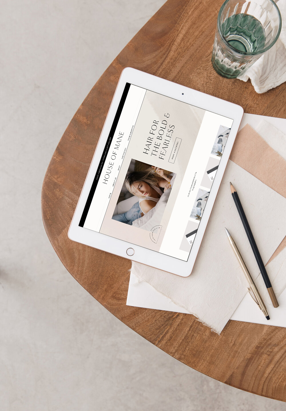 Website for high-end hair salon on a white ipad next to stationery