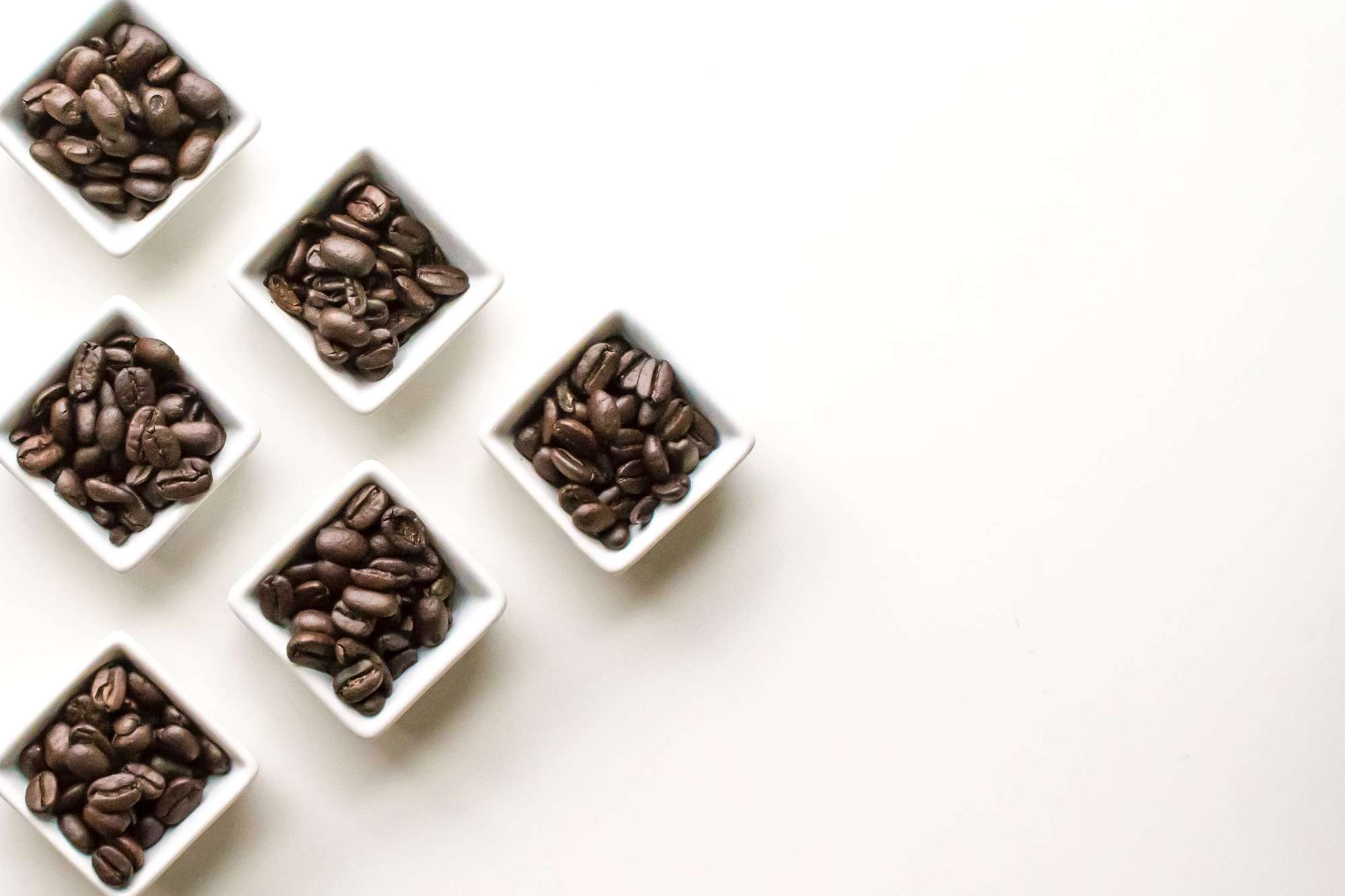 A triangular arrangement of small piles of coffee beans