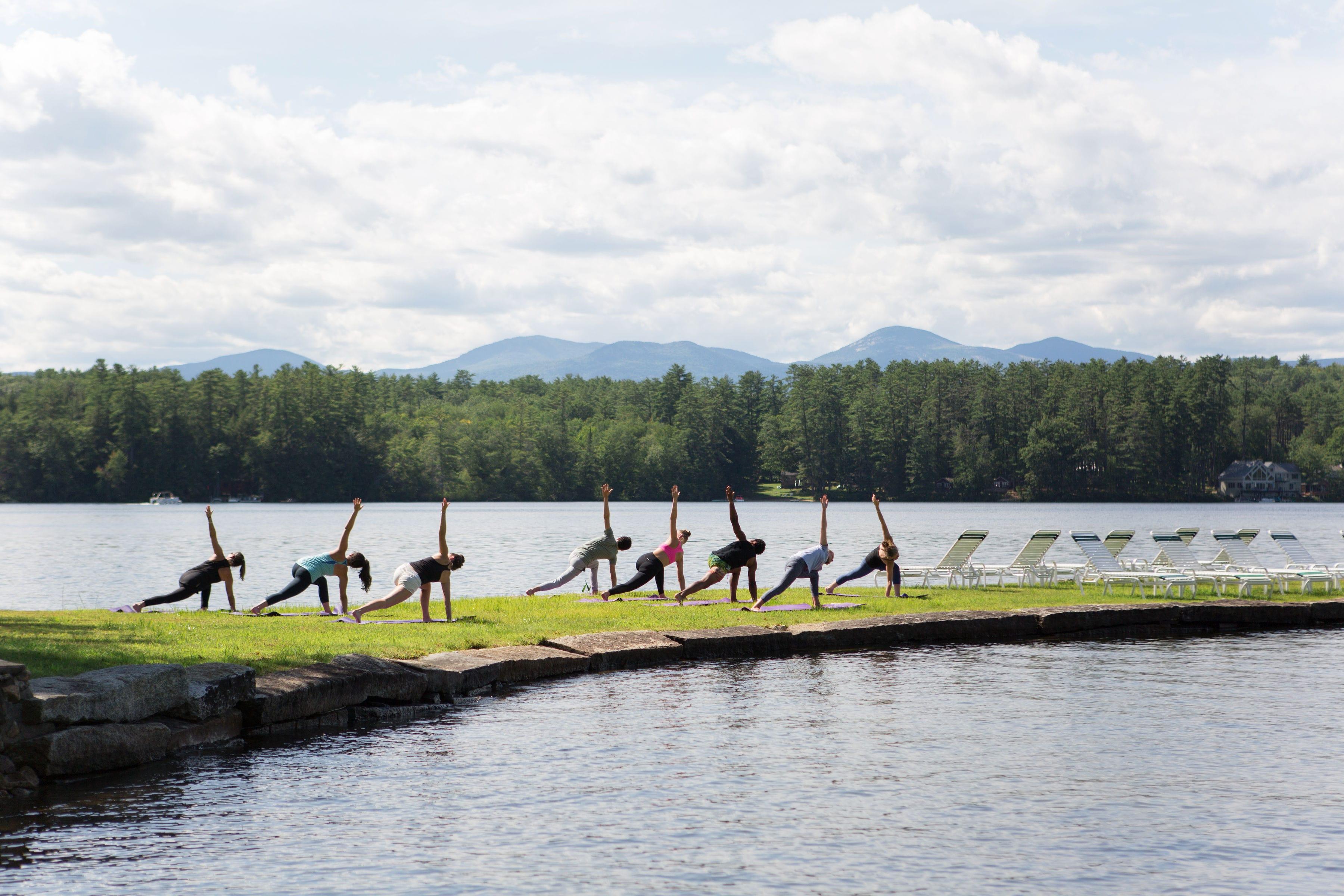 Group of people doing yoga lakeside