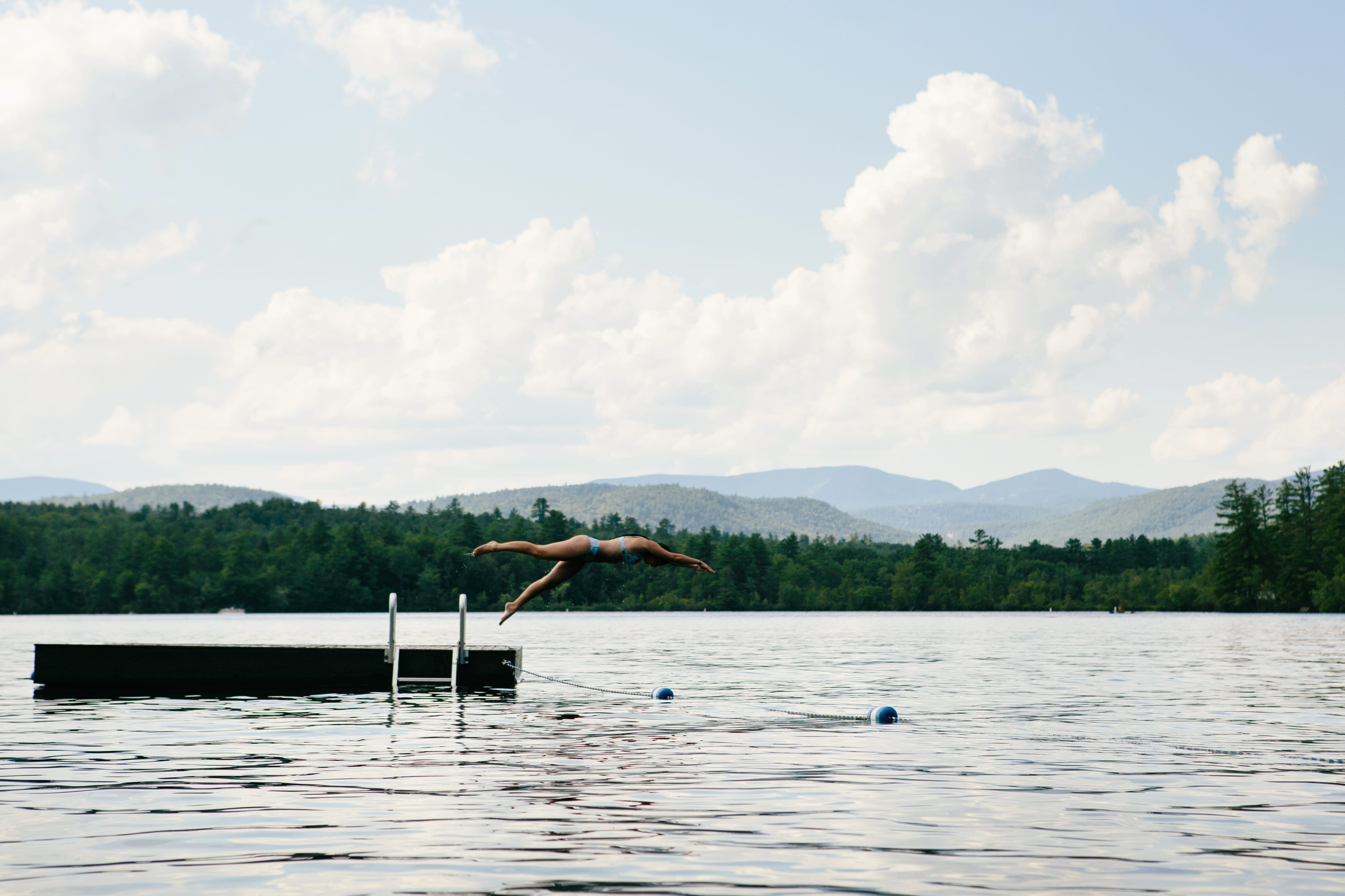 Woman diving off dock into the lake