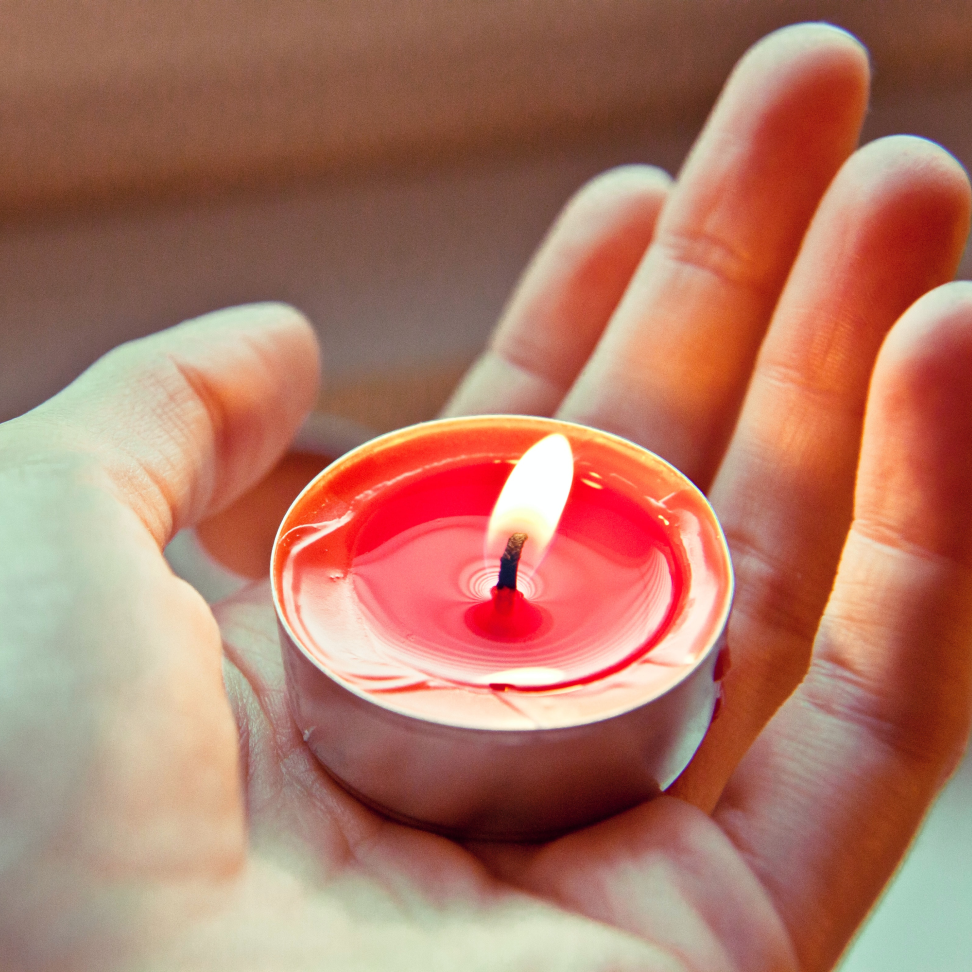 A hand holding a lighted candle