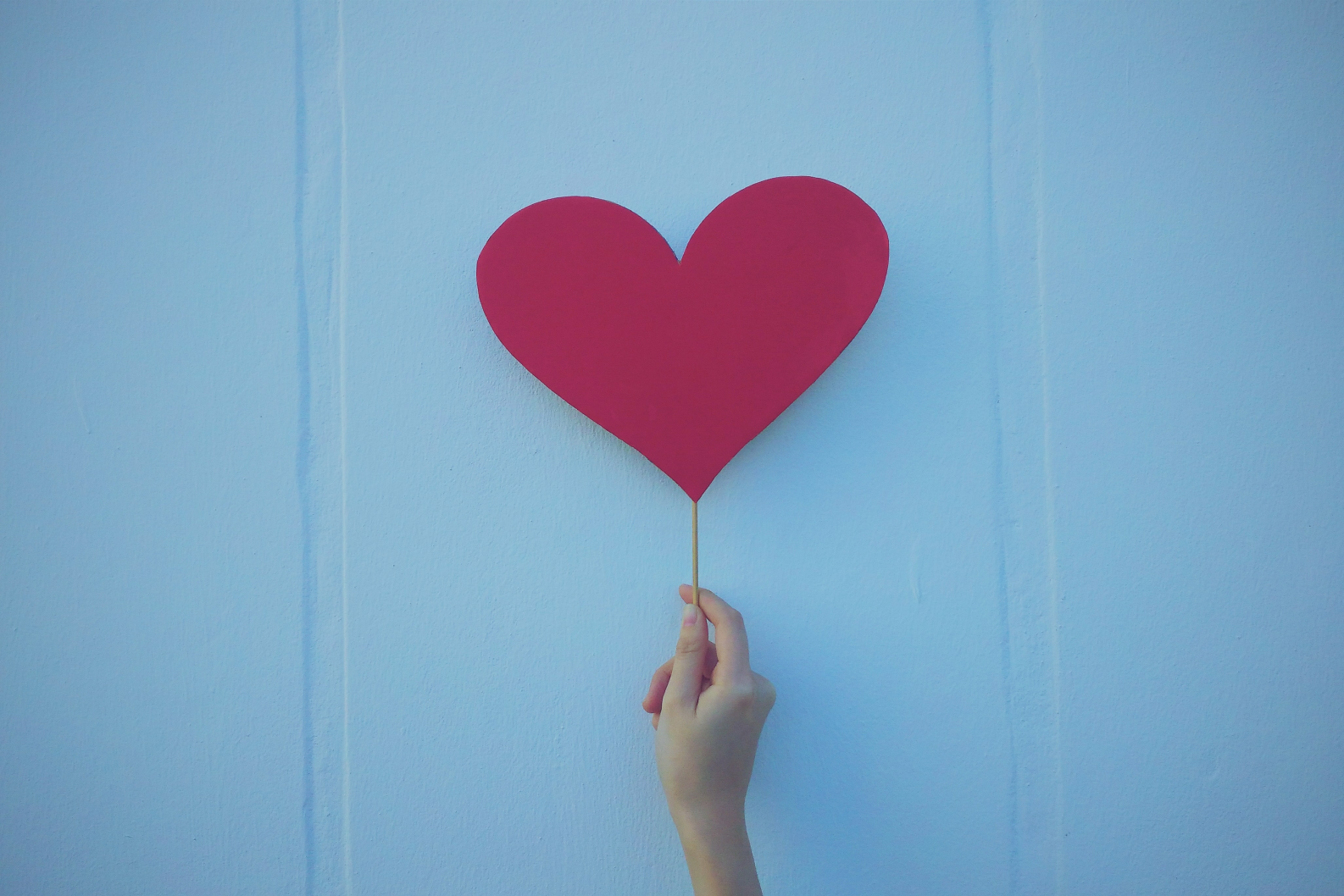 A hand holding out a heart paper cut-out