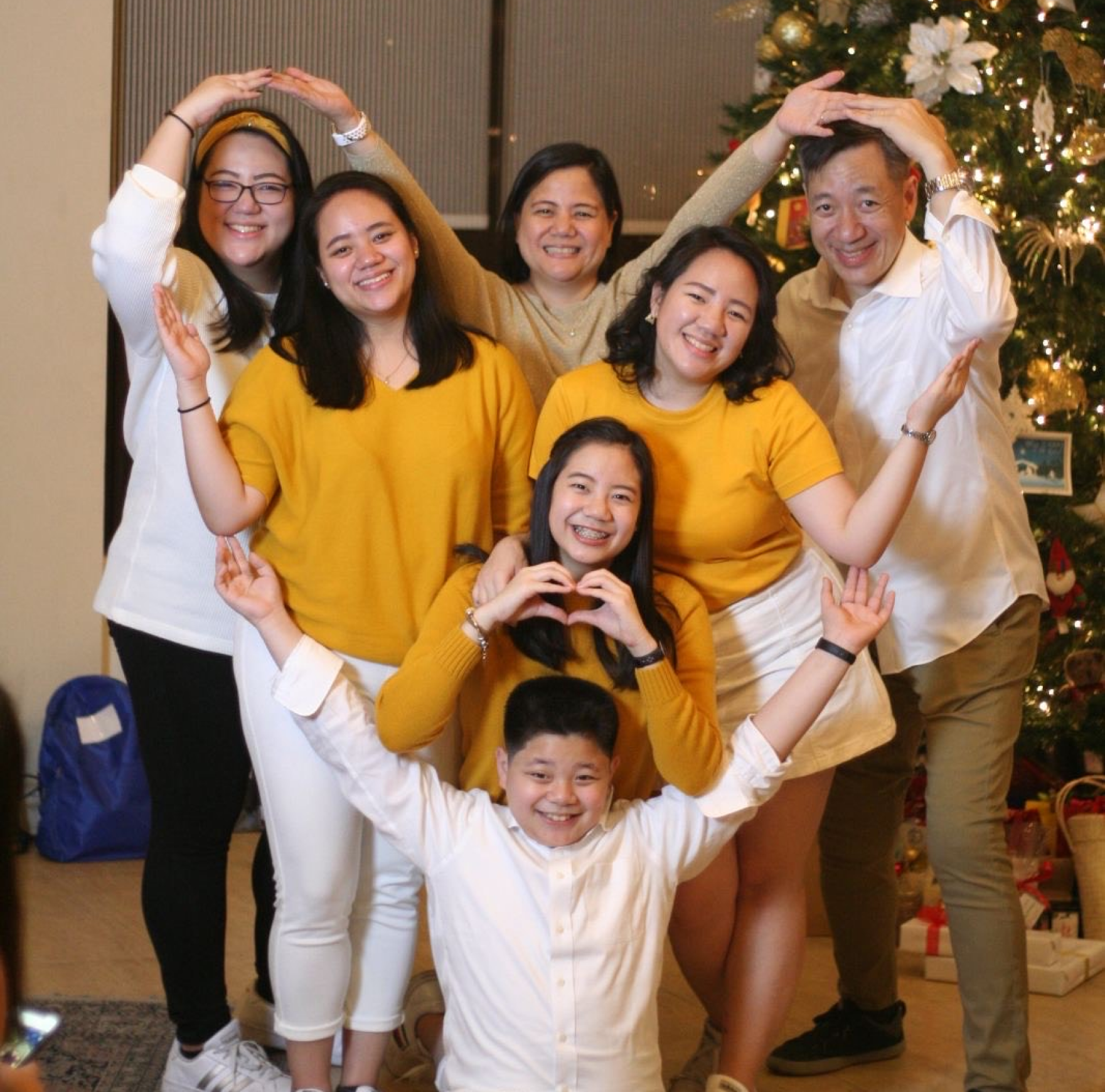 A family of 7 forms a heart shape while smiling