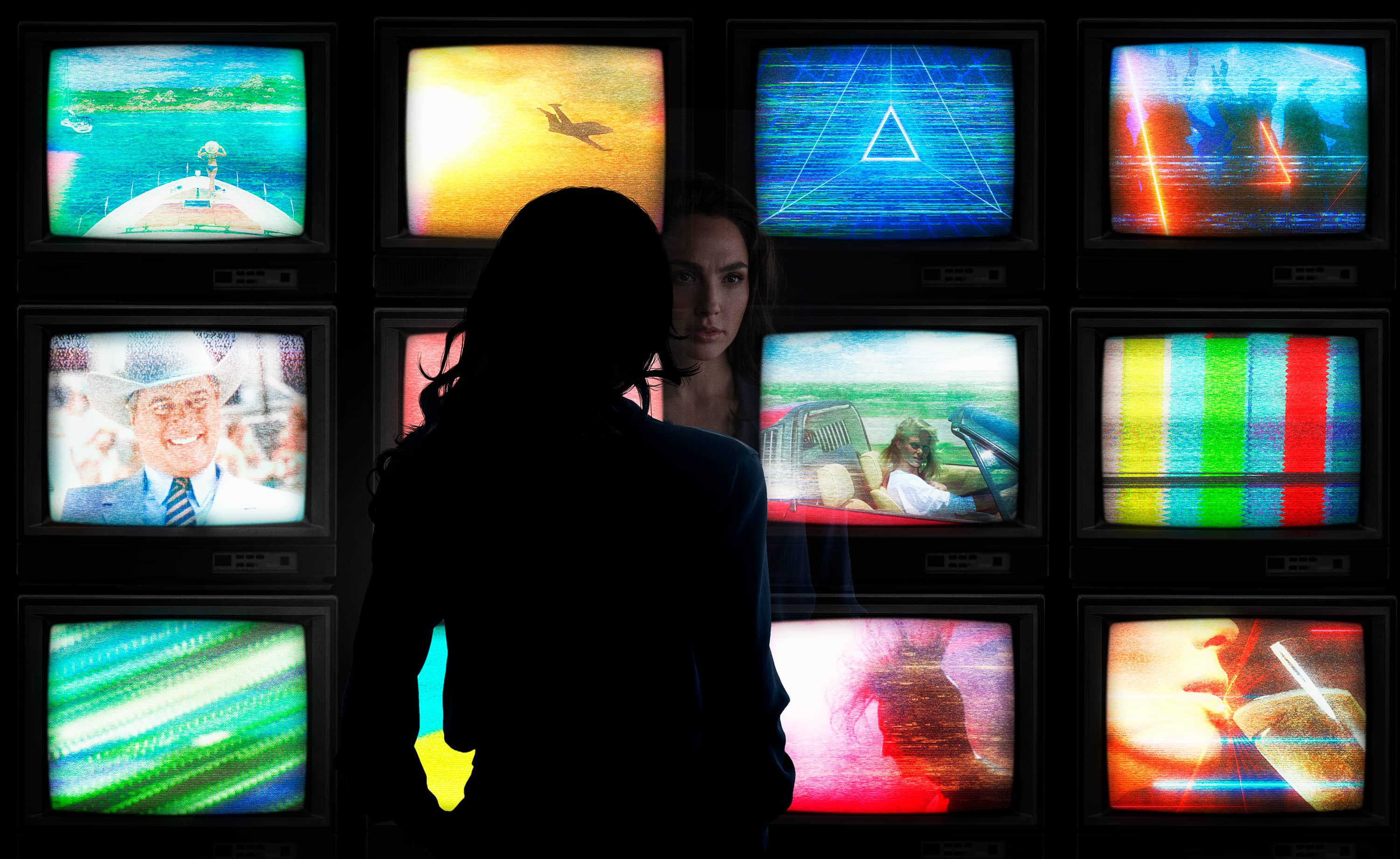 A woman looking at a bank of television monitors (scene from Wonder Woman)