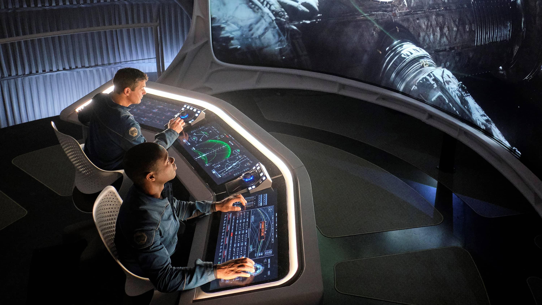 2 men operating spaceship controls