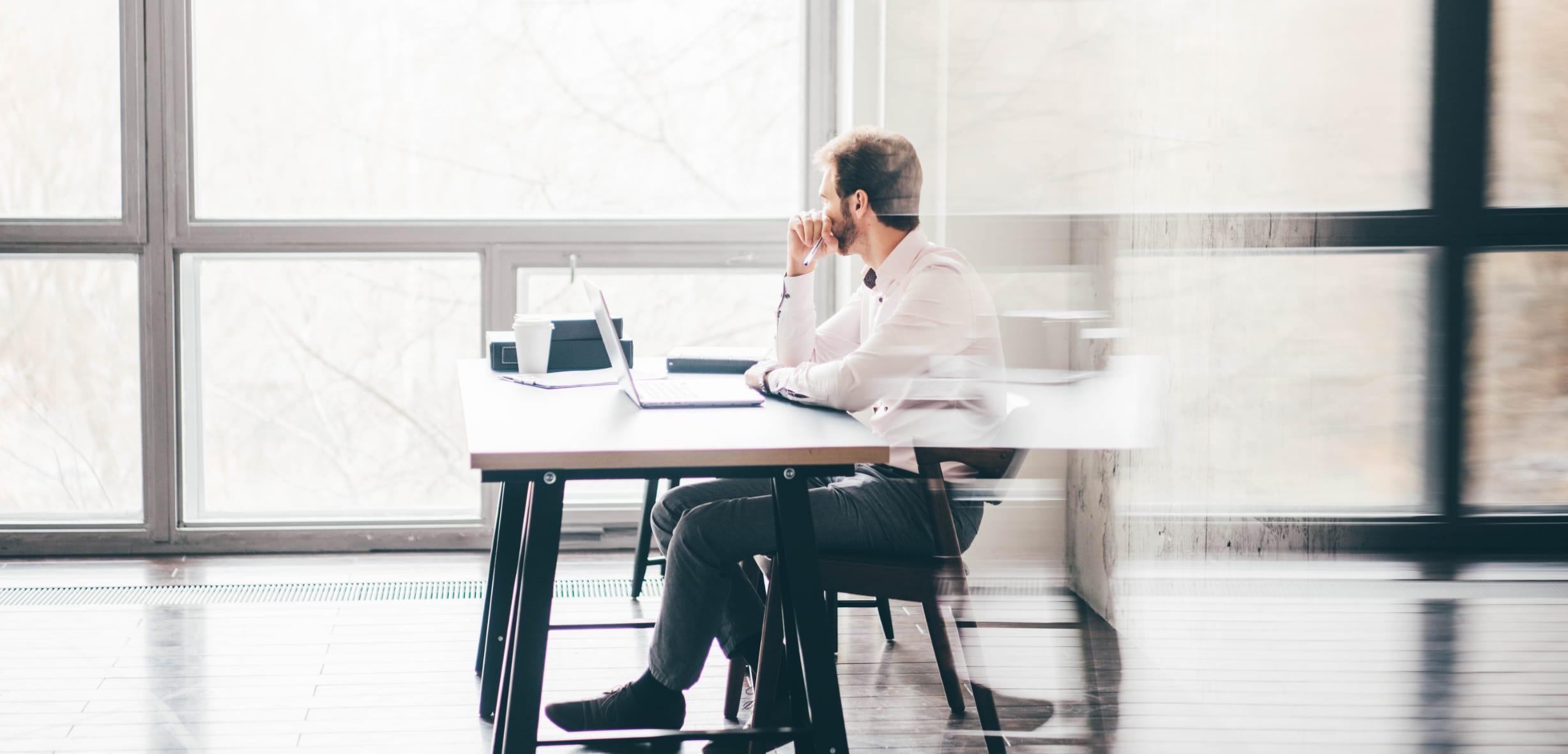 Man staart naar buiten met een opengeklapte laptop voor zich