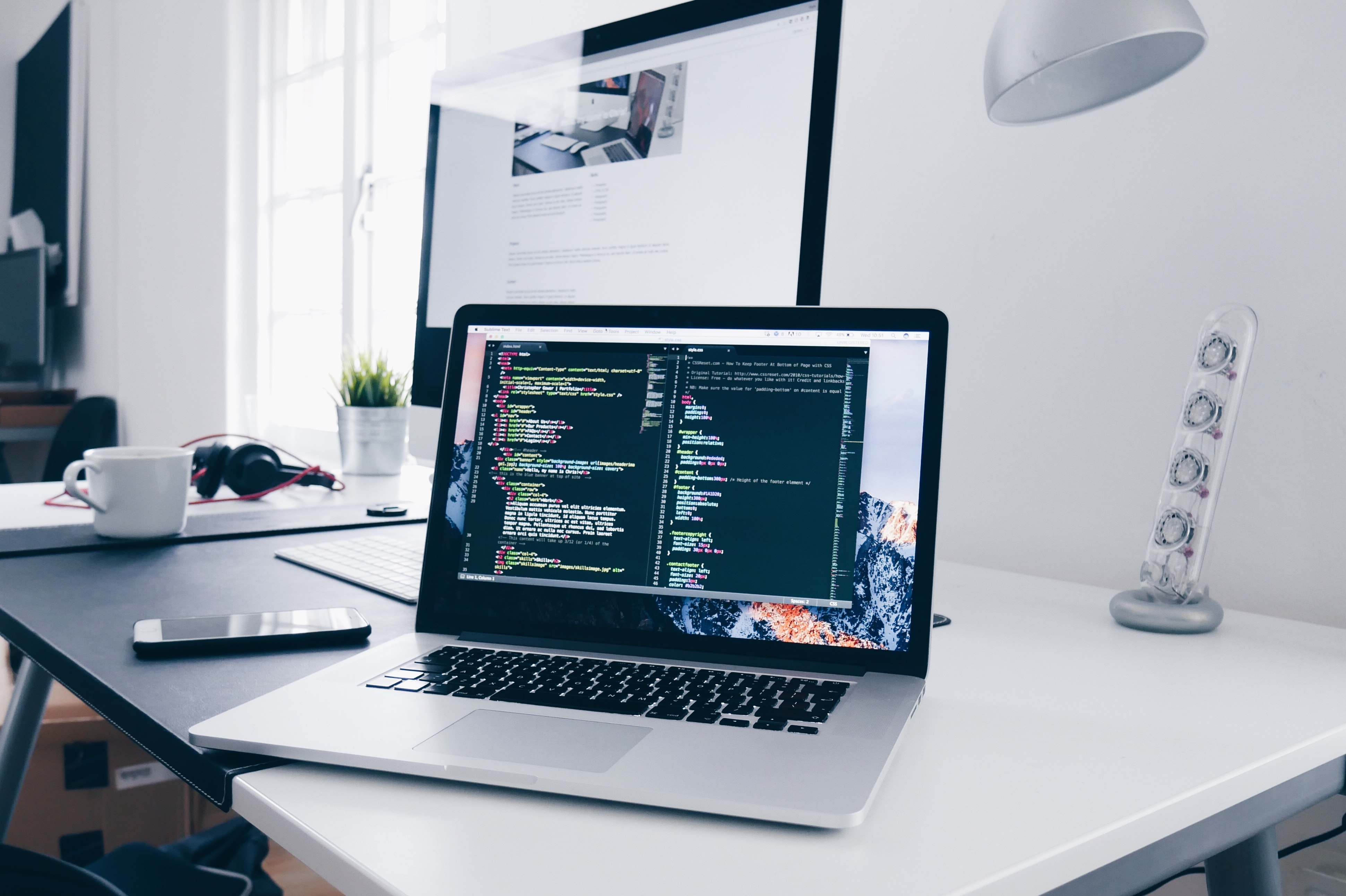 Web developer working on his Macbook using code editor to build a website.