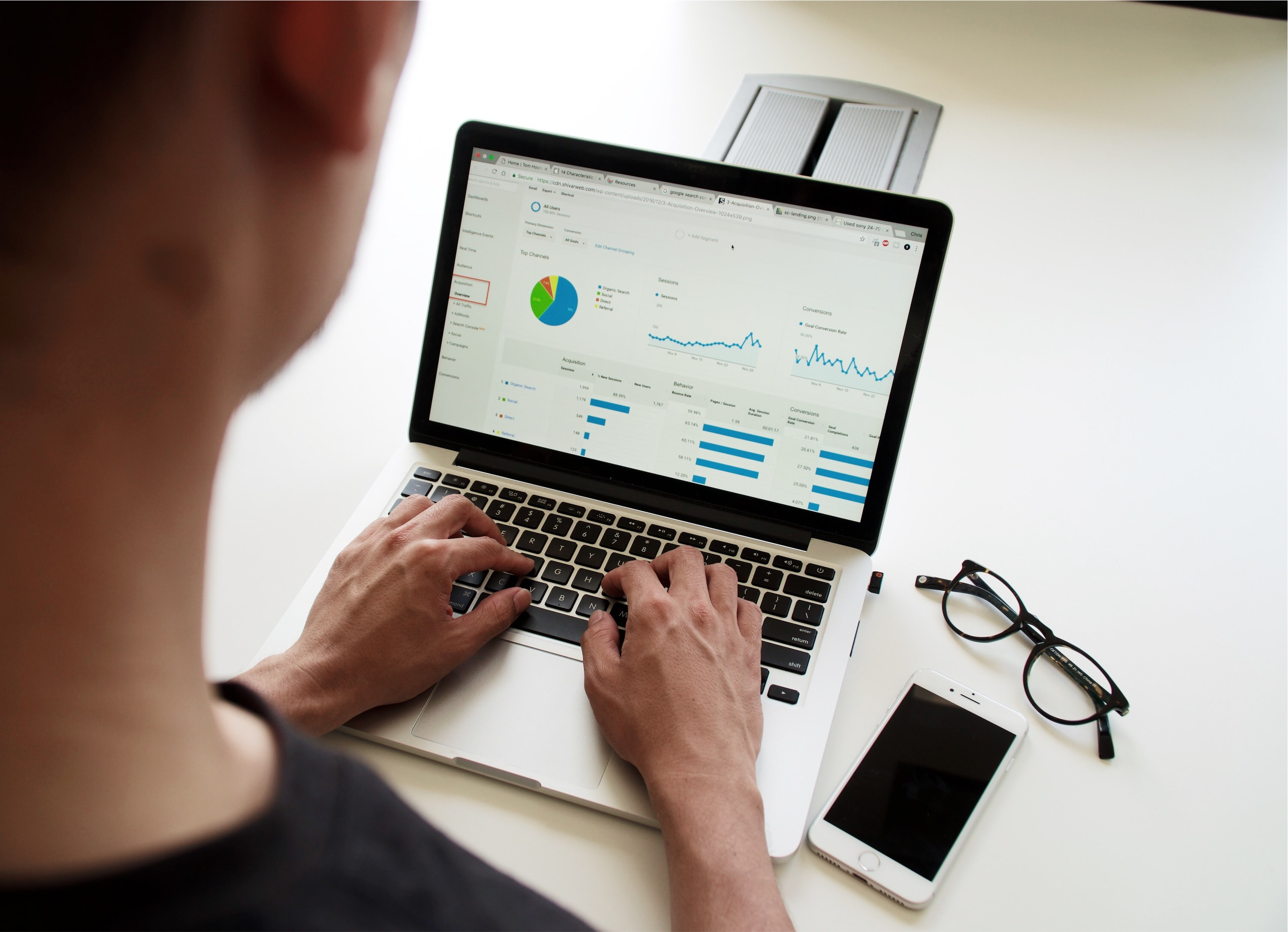 Business owner using macbook pro laptop to look up website analytics using Google Analytics for SEO and organic growth statistics.