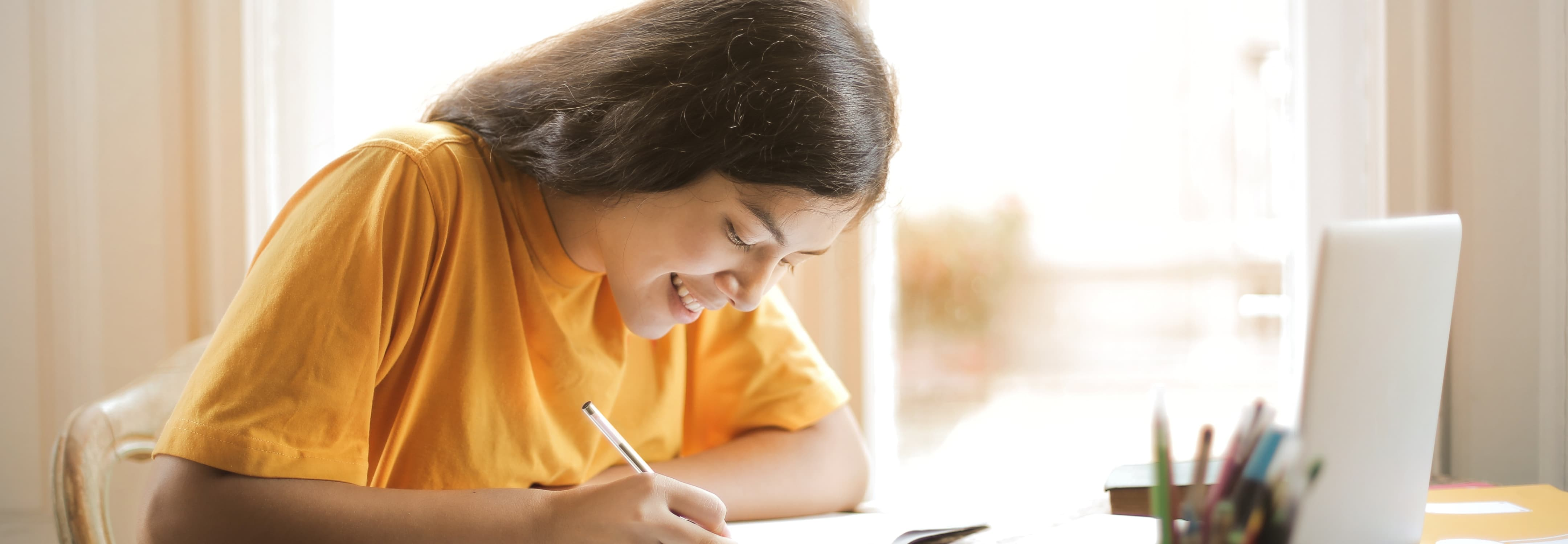 An image of a woman doing homework with a laptop