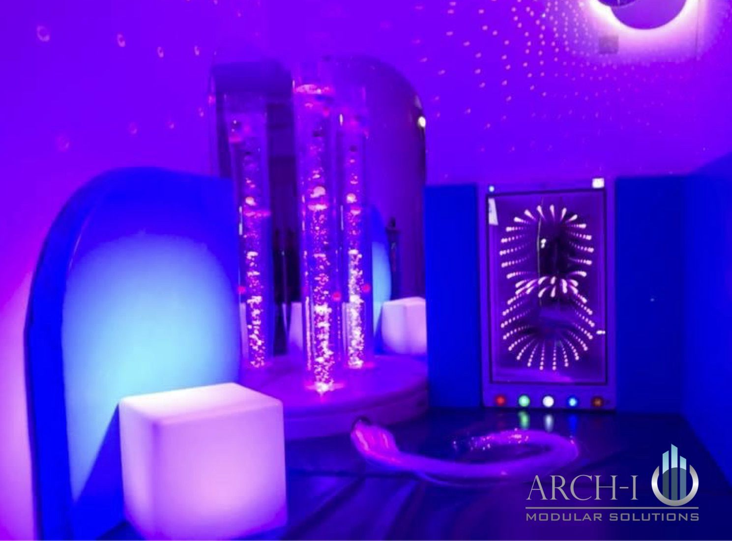 Modular structure functioning as a sensory room with purple and blue light and  water features