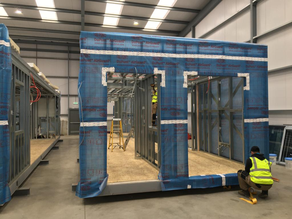 Steel Frame modular structure on factory floor with a man applying insulation.