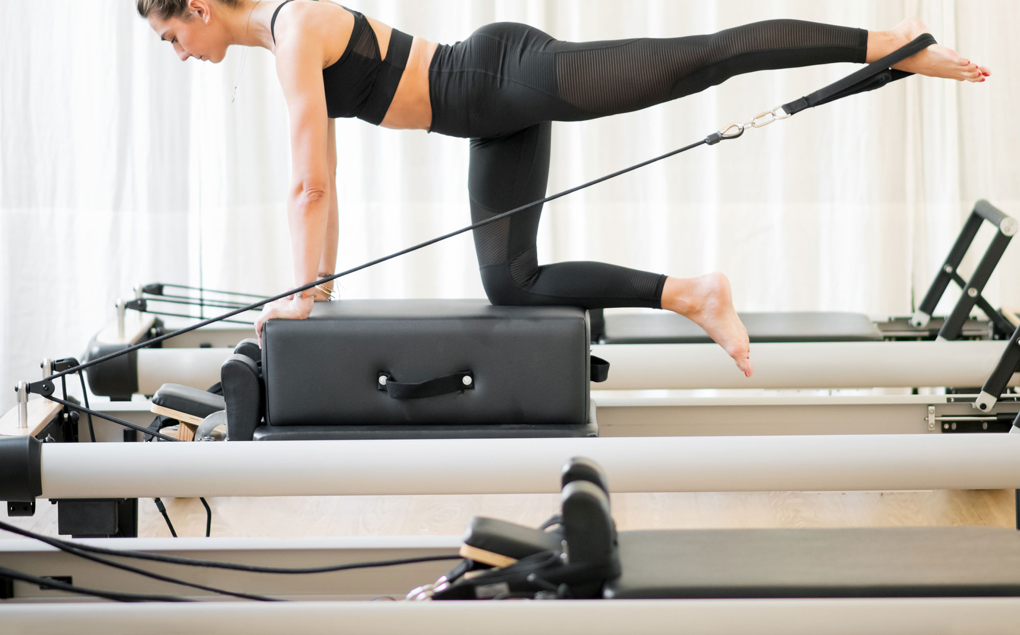 woman doing pilates on reformer head not shown