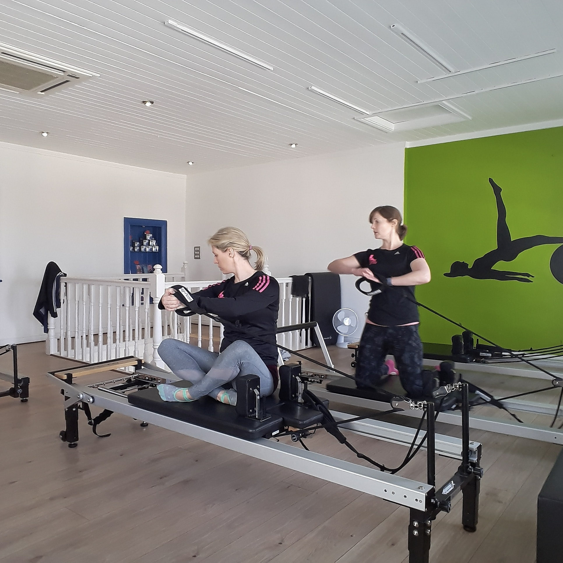 lauras pilates studio two woman doing pilates sitting up on reformer
