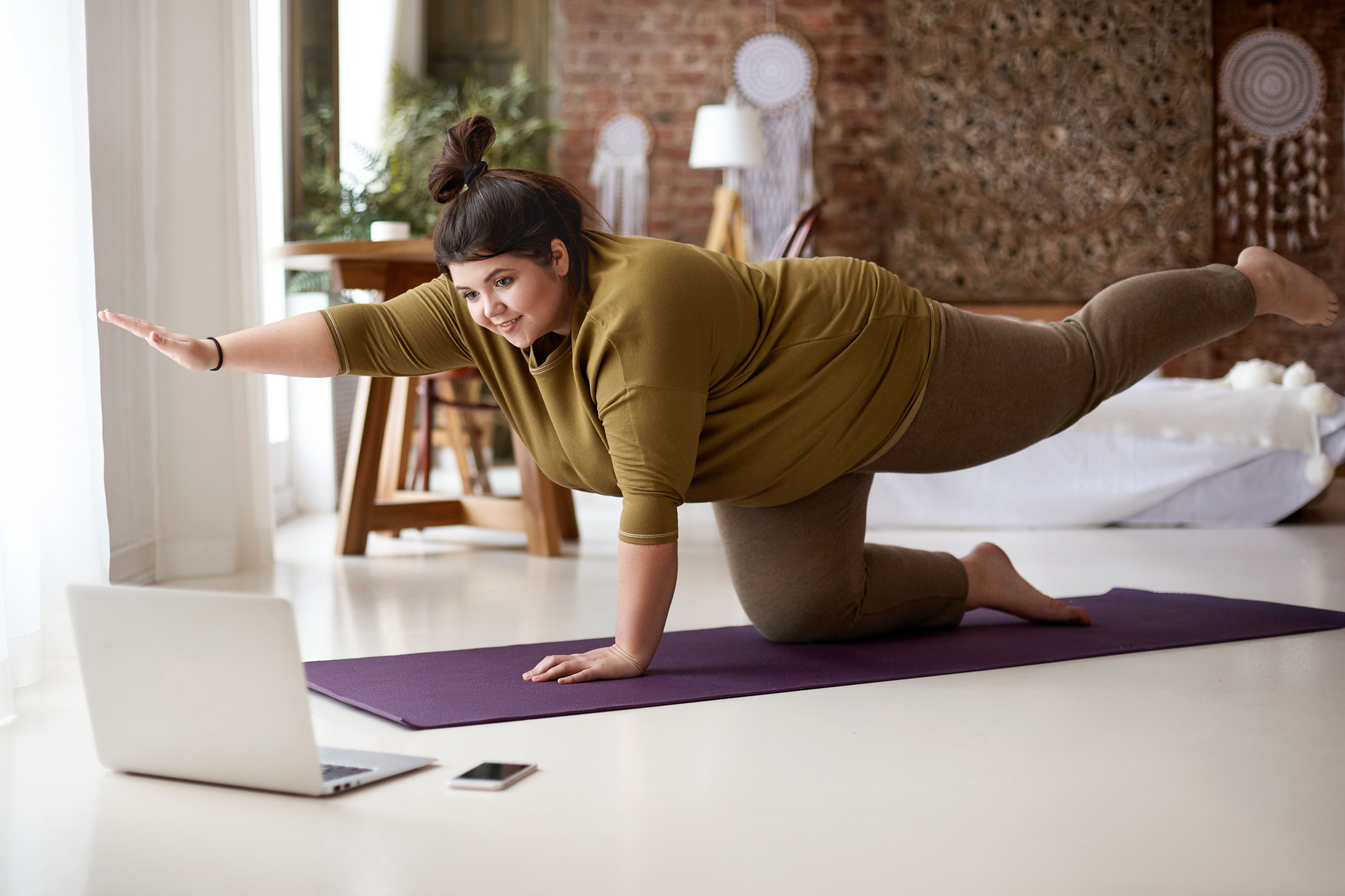 heavy woman doing pilates at home in front of computer