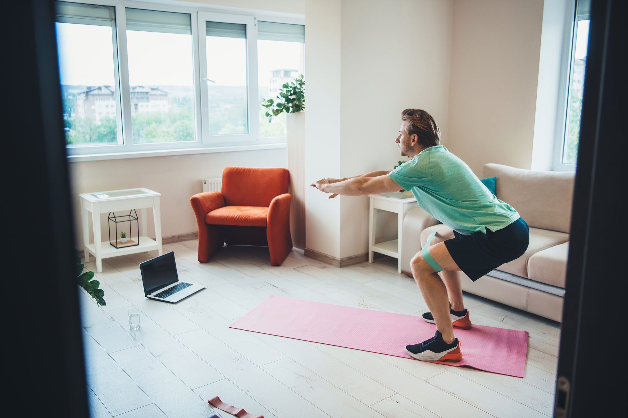 man doing pilates with band around knee at home in front of computer