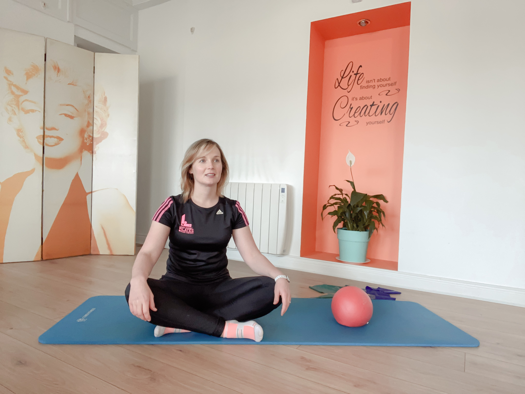 laura harney in studio sitting on mat with pilates props