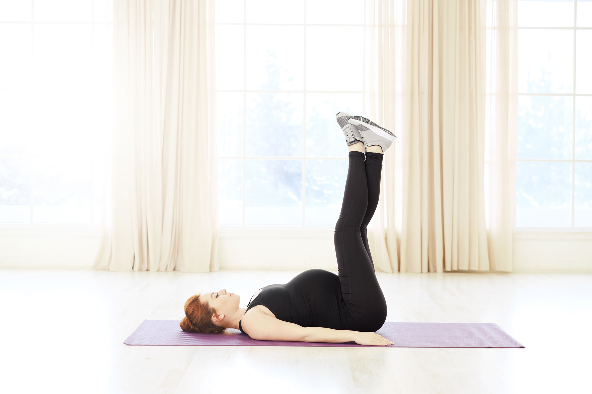 pregnant woman on mat with legs in air doing pilates