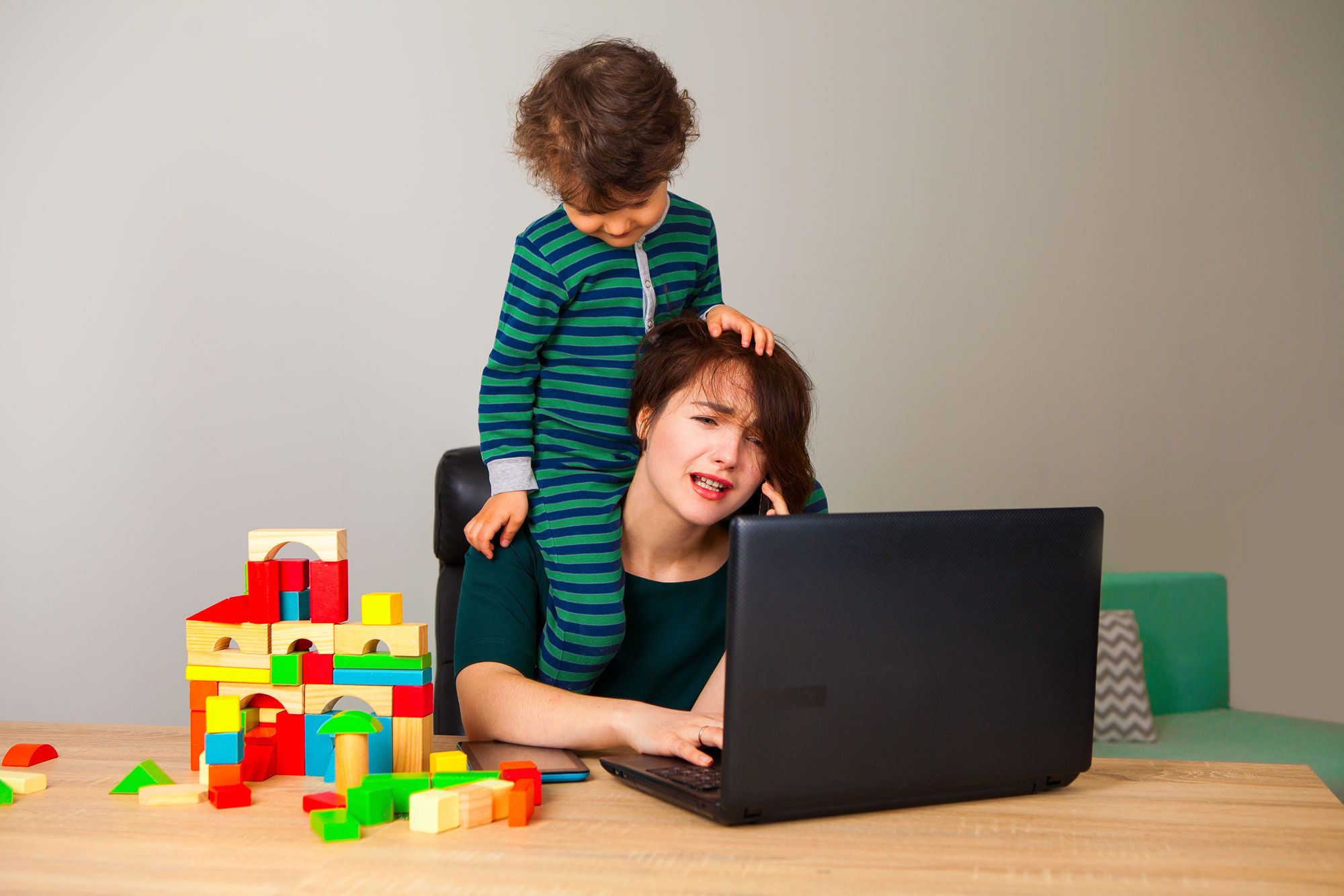 little boy sitting on tired moms shoulder at the table looking at computer