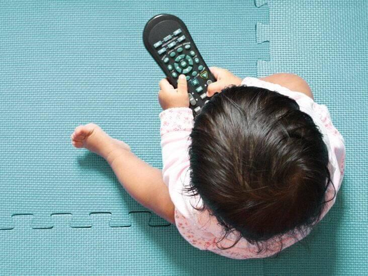 Vừa ăn vừa xem tivi, nghịch điện thoại hoặc đồ chơi là một nguyên nhân gây biếng ăn ở trẻ 1 tuổi