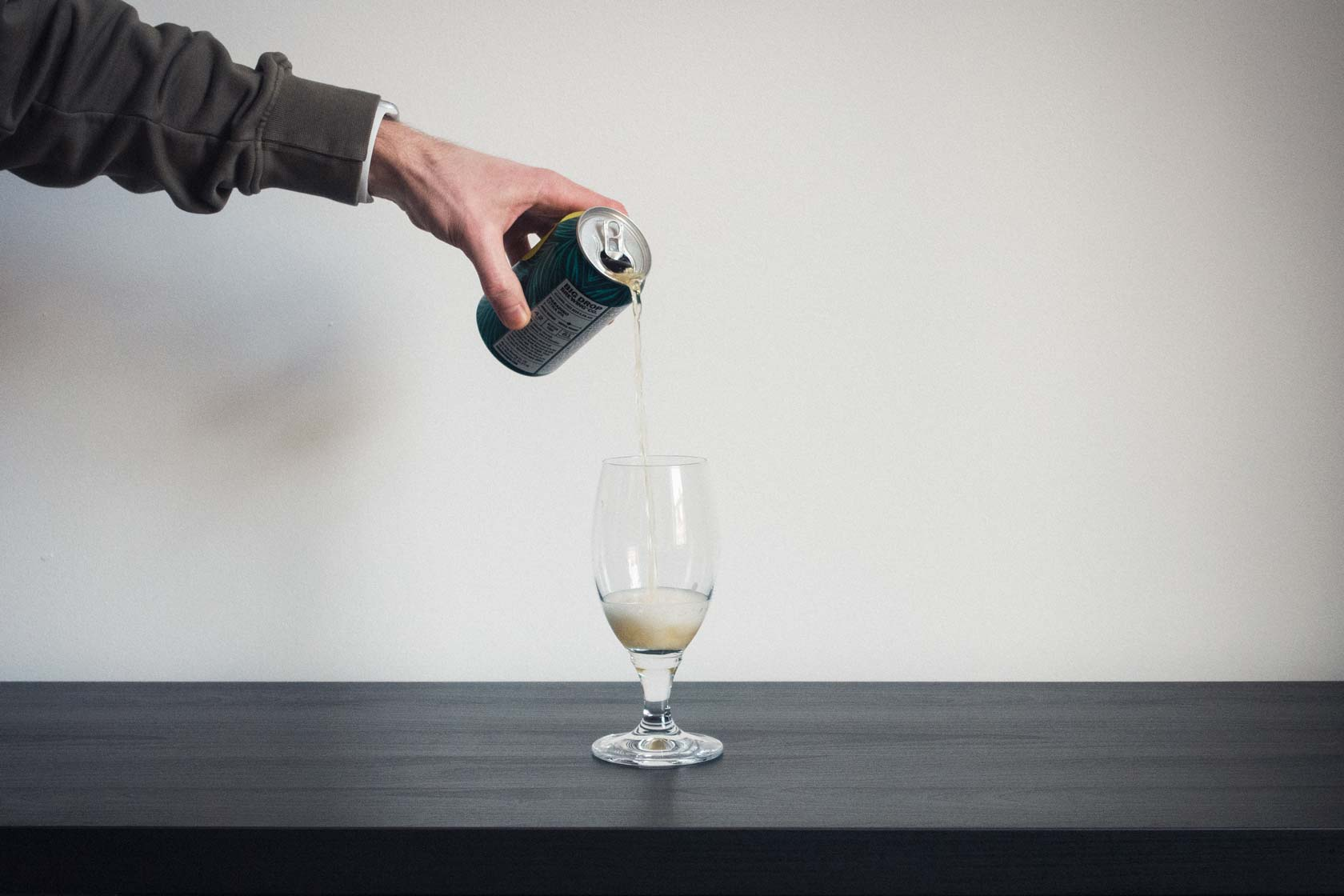beer being poured into glass on minimal desk table