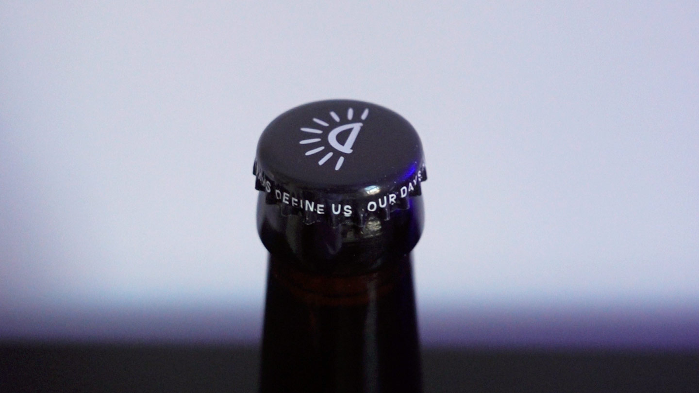 """close up of beer bottle cap that says """"our days define us"""""""