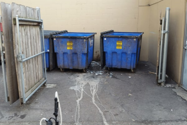 commercial dumpster area before cleaned by pressure washing