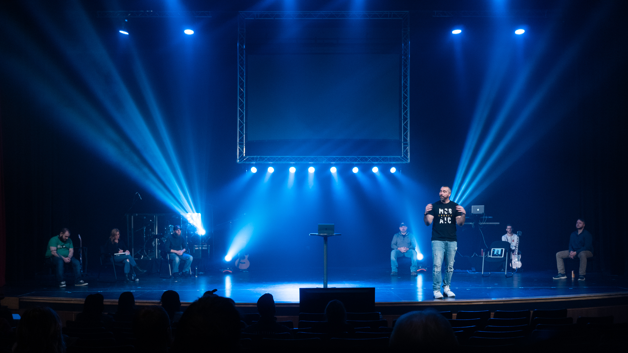 A wide shot of Mosaic's Worship Experience. Pastor Adam Barton is preaching on stage while members of Mosaic Worship are sitting on stage, behind him, watching, and very engaged.