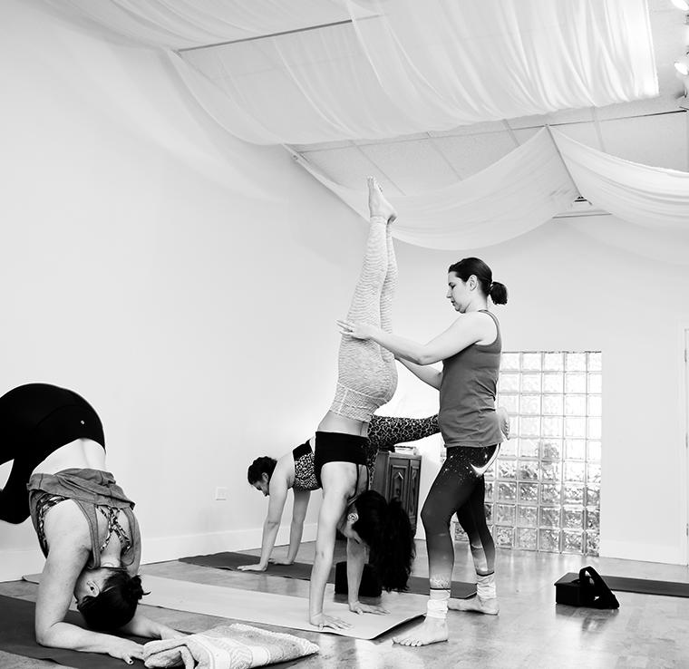 A yoga teacher helping a student do a handstand