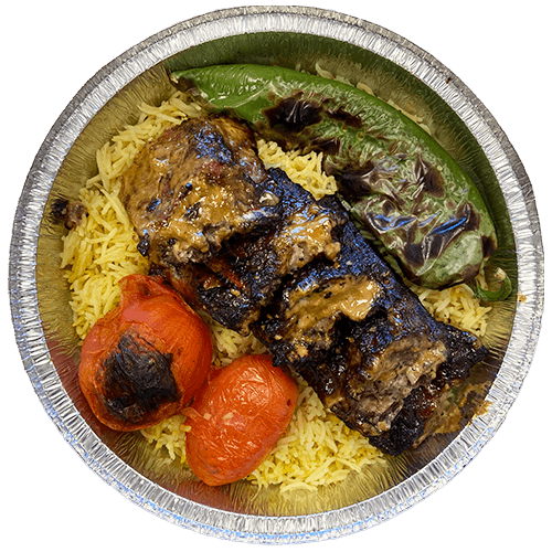 An image of grilled pork ribs on a bed of Saffron Basmati Rice with two grilled tomatoes and a grilled Poblano pepper.