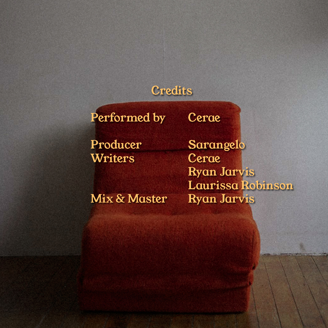 An orange chaise against a white wall and hard wood floor. There is yellow text over the image which lists the members of the production team and their roles.