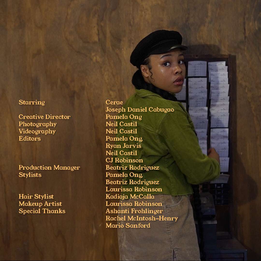 Cerae looking back over her shoulder while she punches in a card into a vintage punch clock. She is wearing a green jacket, black conductor hat and a brown skirt. There is yellow text over the image which lists the members of the production team and their roles.