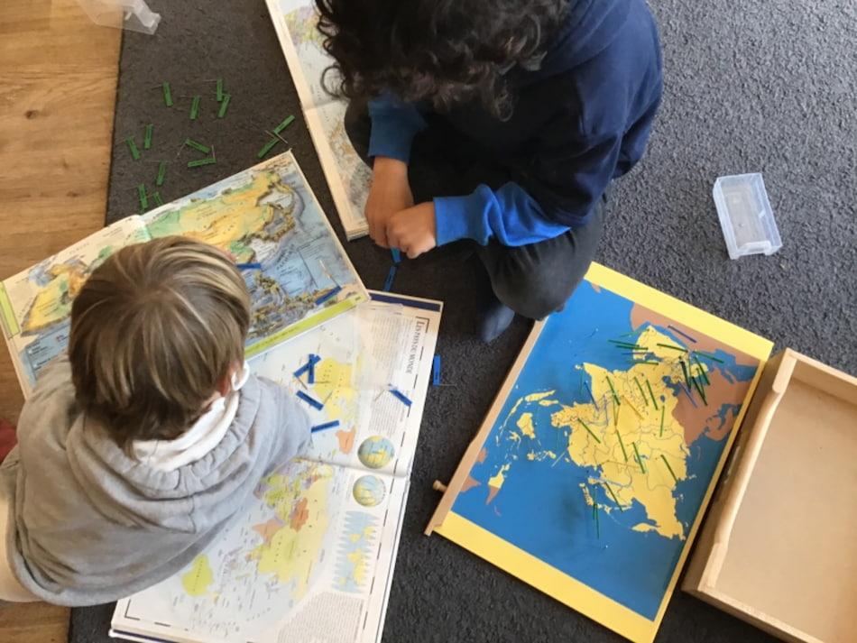 Des enfants à l'école, avec des cartes de géographie