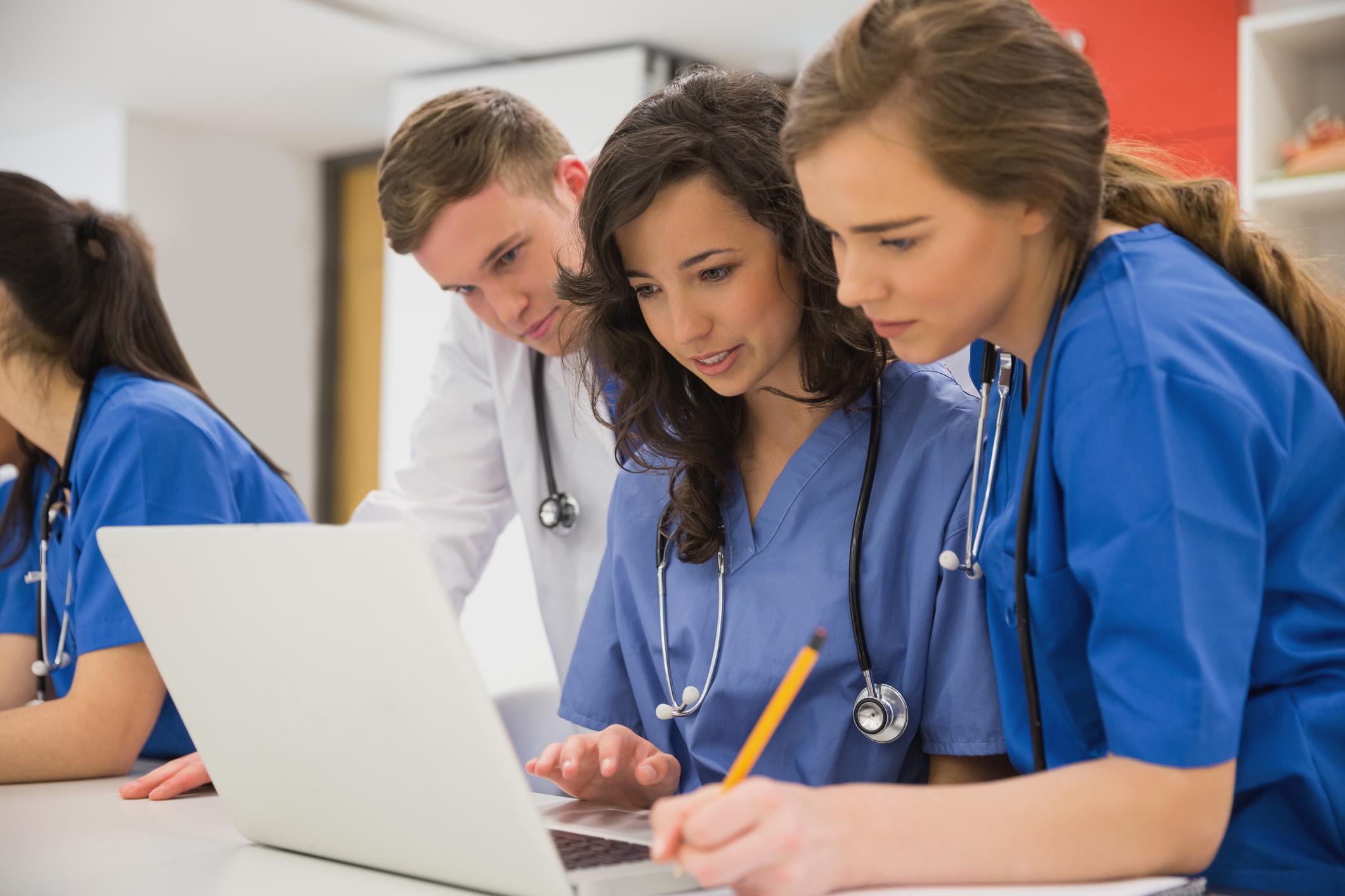 Three medical students looking at a laptop