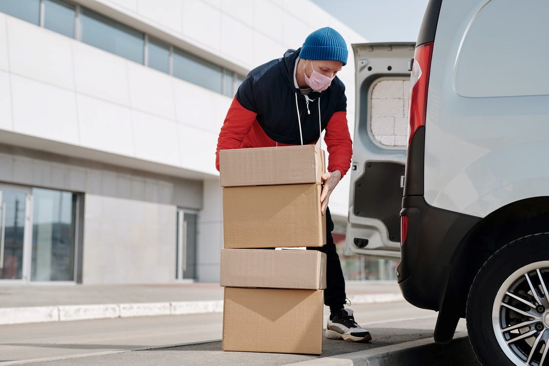 Delivery person wearing a mask and carrying boxes