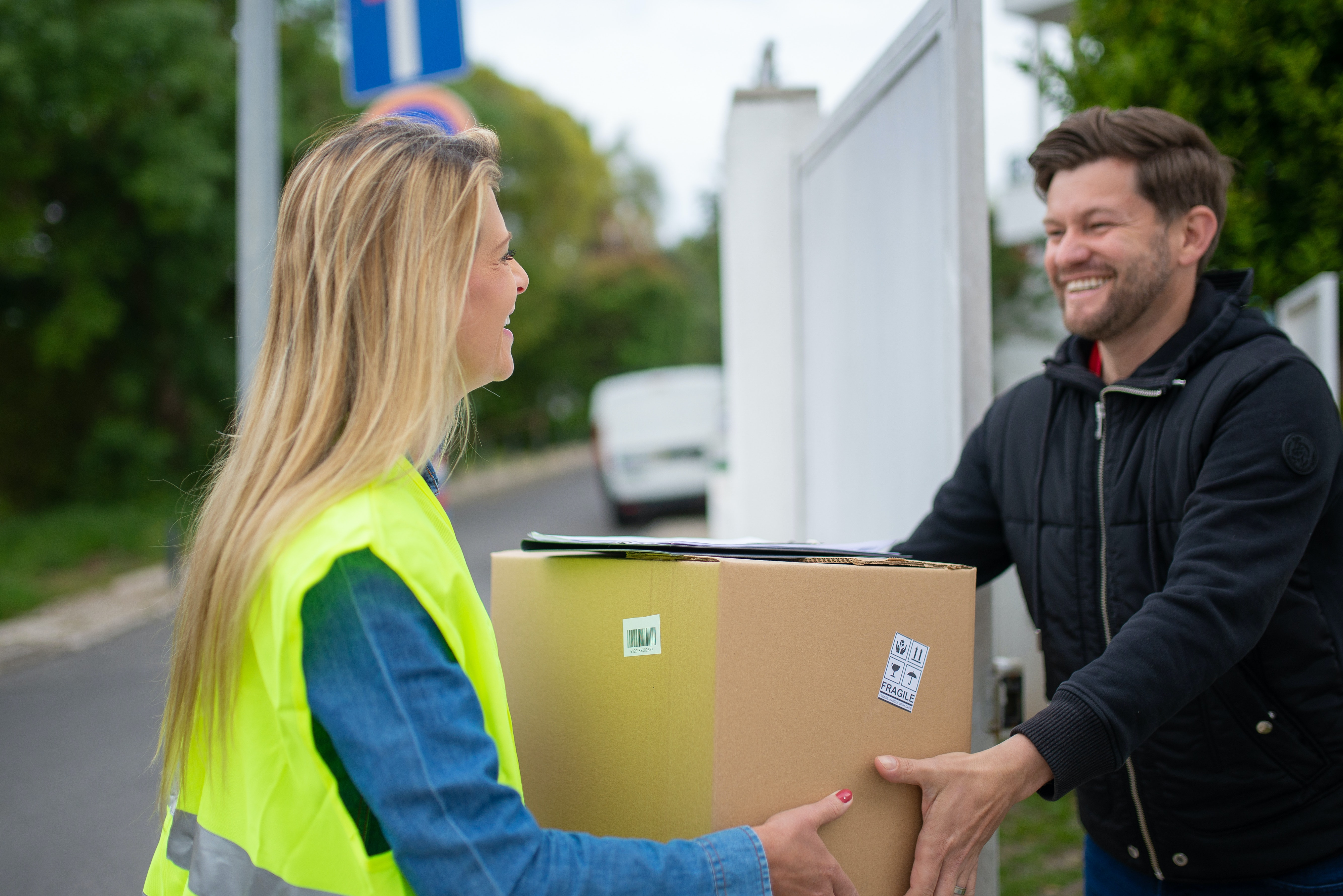 a man receiving a parcel from  delivery woman